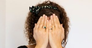 Naomi met haar handen voor haar ogen
